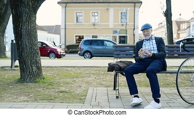 Senior man with bicycle and smart phone, making phone call -...