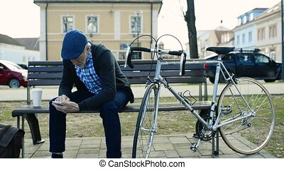 Senior man with bicycle in town, holding smart phone,...