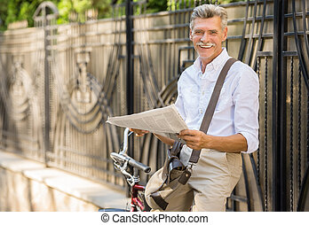 Senior man with bicycle - Senior man is reading newspaper...