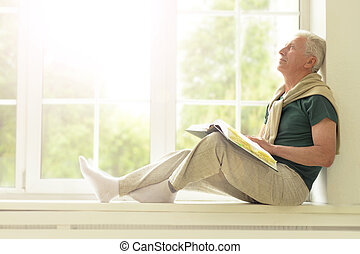 Senior man with book at home - Senior man with book sitting...