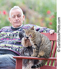 Senior man with cat and dog
