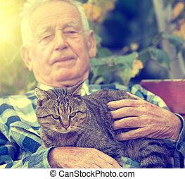 Senior man with cat in courtyard