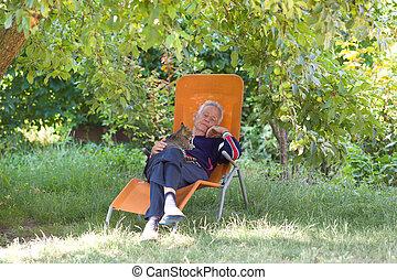 Senior man with cat in garden