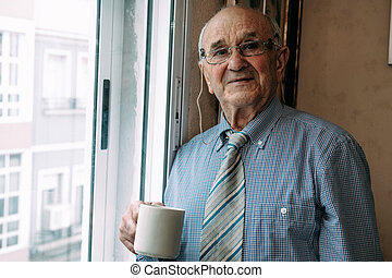 senior man with cup of coffee at home looking out the window