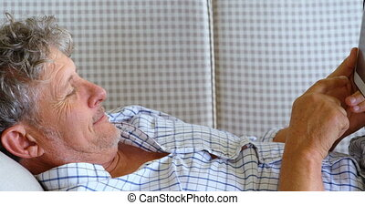 Senior man with digital tablet lying on sofa on the porch 4k...