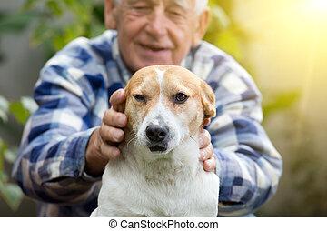 Senior man with dog in courtyard