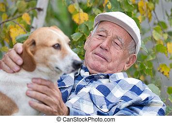 Senior man with dog in courtyard - Senior man sitting on ...