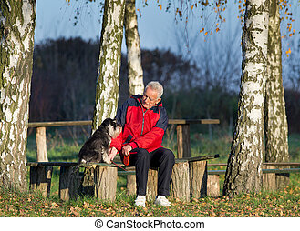 Senior man with dog in the park - Senior man with Miniature...