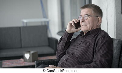 Senior man with eyeglasses talking on the phone and sitting ...