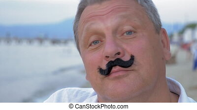 Senior man with fake mustache - Close-up shot of a mature...