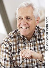 Senior Man With Glasses Relaxing In Chair At Home
