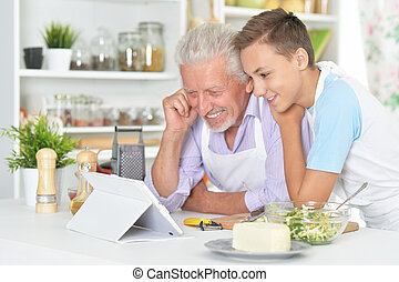 Senior man with grandson preparing dinner