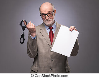 Senior man with handcuffs and paper