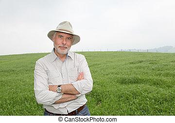 Senior man with hat in farmland
