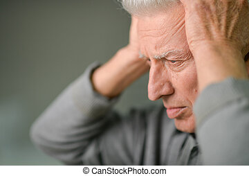 Senior man with headache holding