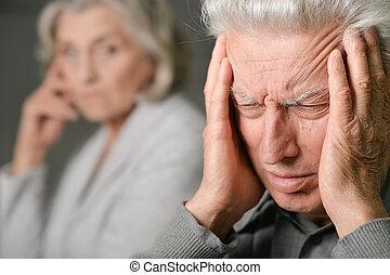 Senior man with headache holding