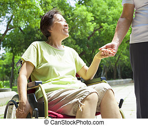 senior man with her disabled wife on wheelchair