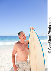 Senior man with his surfboard