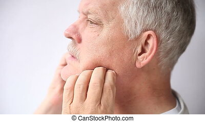 an older man experiencing pain either in his teeth or jaw joint