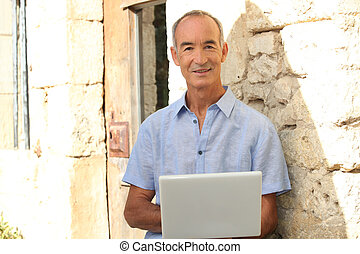 Senior man with laptop in front of stone house