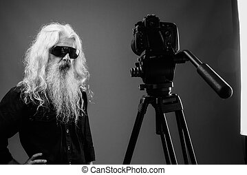 Senior man with long hair and beard vlogging in black and white