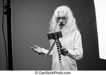 Senior man with long hair and beard vlogging with phone in black and white