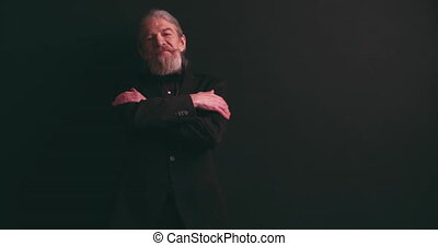 Senior man with long whitened hair and beard in dark business clothes fixing his jacket and tup arms crossed standing in semi-lit room on black background. Mature man on black background. Prores 422.