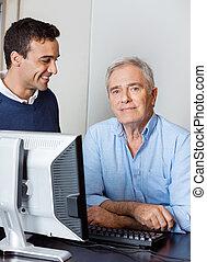 Senior Man With Male Teacher In Computer Class