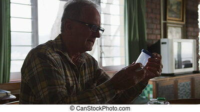 Senior man with medical drugs at home - Side view of a...