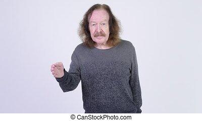 Senior man with mustache giving handshake - Studio shot of...