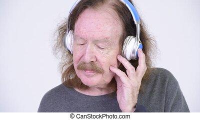 Senior man with mustache listening to music