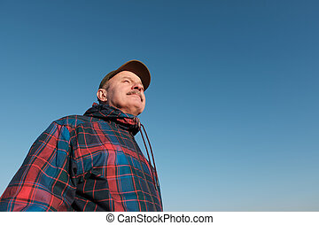 Senior man with mustache looking at camera against gblue sky...