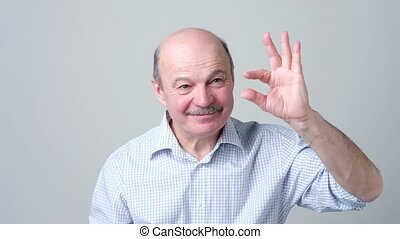 Senior man with mustache showing something small with...