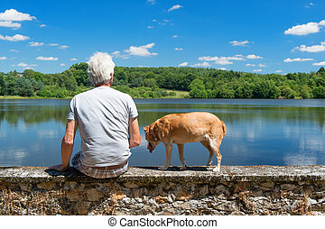 Senior man with old dog in nature landscape