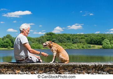 Senior man with old dog in nature landscape