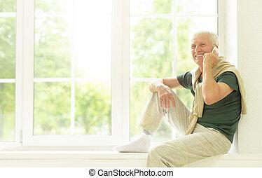 senior man with phone at home