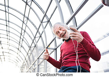 Senior man with smartphone and headphones in passage.
