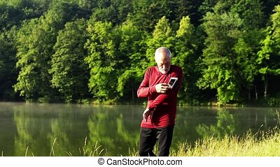 Senior man with smartphone walking by the lake outdoor in...