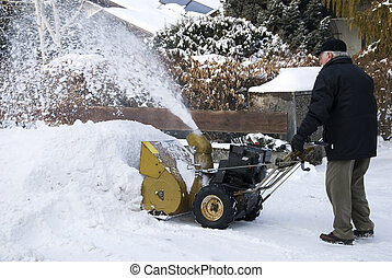 senior man with snow blower in wintertime