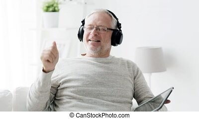 senior man with tablet pc and headphones at home 91