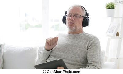 senior man with tablet pc and headphones at home 14