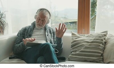 Senior man with tablet relaxing at home. Old man listening...