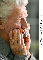 Senior man with toothache holding