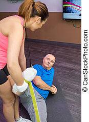 senior man with trainer in fitness studio