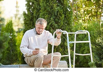 Senior Man with Walker Resting in Park