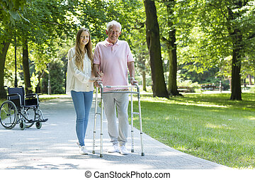 Senior man with walking frame accompanied by caregiver