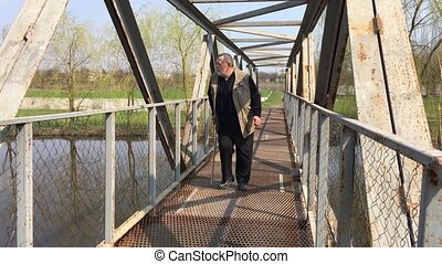 Disabled bearded senior man with walking stick moving slow and watching around on metal bridge over small river