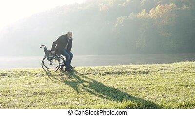 Senior man with wheelchair in autumn nature. - Senior man...
