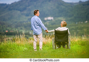 Senior man with woman sitting in wheelchair, holding hands, oustide in green autumn nature, rear view