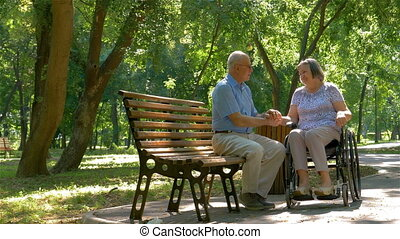 Senior man with woman in wheelchair outside in park